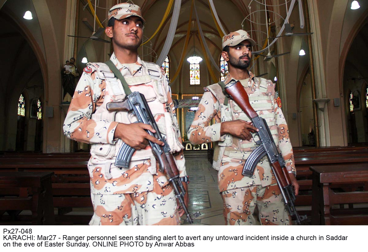Px27-048 KARACHI: Mar27 - Ranger personnel seen standing alert to avert any untoward incident inside a church in Saddar on the eve of Easter Sunday. ONLINE PHOTO by Anwar Abbas