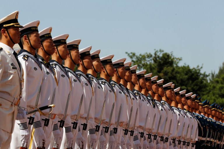 Chinese military troops stand at attention for the visit of US Secretary of Defense Leon Panetta at the Bayi Building in Beijing on September 18, 2012.  Panetta, who was in Tokyo the day before, was to deliver an appeal for calm in talks with senior Chinese military leaders amid an escalating territorial dispute between Beijing and Tokyo.      AFP PHOTO / POOL / Larry Downing