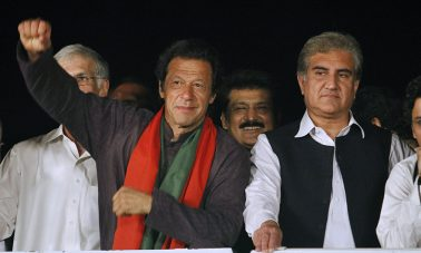 Pakistan's cricketer-turned-politician Imran Khan, left, raises his arm before his supporters as his party leader Shah Mahmood Qureshi, right, looks on during a protest in Islamabad, Pakistan, Wednesday, Sept. 3, 2014. Negotiators for thousands of protesters demonstrating outside of Pakistan's parliament met Wednesday with Pakistani politicians trying to end the crisis but key challenges appear to remain, including the protesters' demand that Prime Minister Nawaz Sharif resign. (AP Photo/Anjum Naveed)